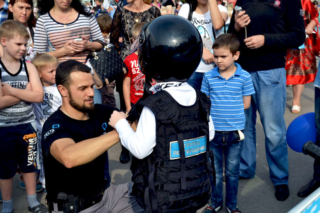 Охранник помогает школьнику одеть шлем и бронежилет